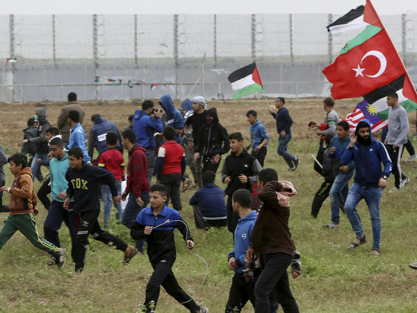 Protesters run to cover from teargas fired by Israeli troops near fence of Gaza Strip border with Israel on Saturday. The day marked the first anniversary of the Gaza border protests.