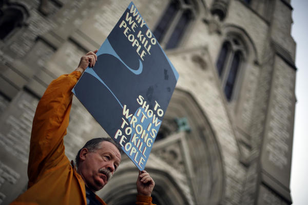 Death penalty opponent Herve Deschamps holds a sign during a vigil outside St. Francis Xavier College Church in St. Louis, hours before the 2014 scheduled execution of death row inmate Russell Bucklew.