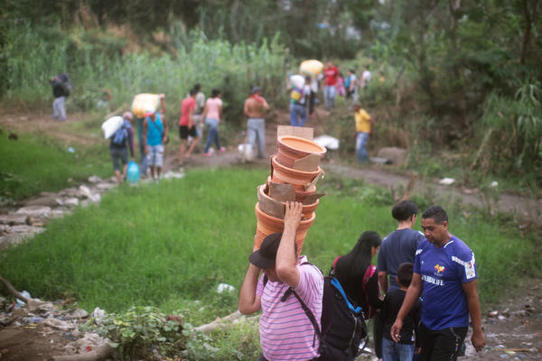 People walk from Venezuela to Colombia through an unauthorized border crossing in Villa del Rosario, Colombia. Some 3.4 million Venezuelans are seeking refuge abroad, with more than 1 million of them in neighboring Colombia, according to the United Nations refugee agency, UNHCR. Many people are leaving Venezuela by foot.