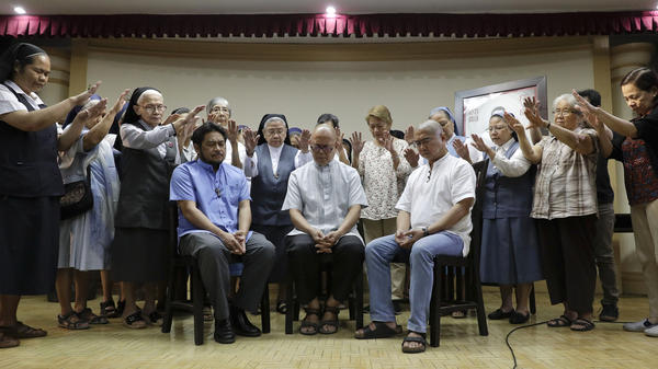 Filipino Catholic priests (seated from left) Albert Alejo, Robert Reyes and Flavie Villanueva are prayed over by nuns and religious leaders after talking to reporters in Quezon City, north of Manila, Philippines, on March 11. The three priests say they and other clergy who have criticized the president's crackdown on drugs, have received death threats from unknown people.