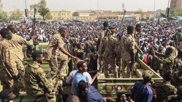 Sudanese soldiers stand guard on armored vehicles as demonstrators protest against President Omar al-Bashir's regime near the army headquarters in the Sudanese capital Khartoum Thursday.
