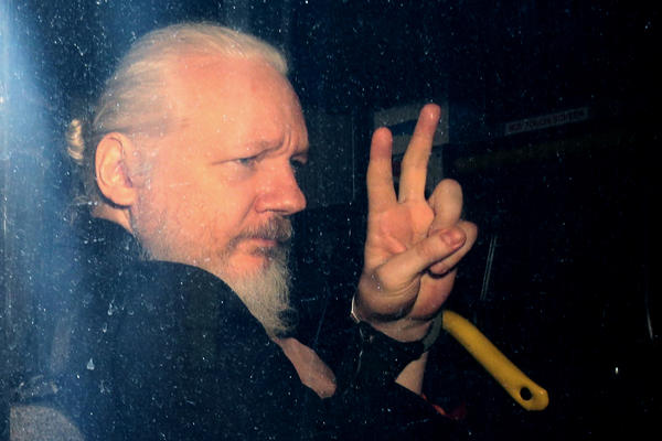 WikiLeaks founder Julian Assange arrives in a police vehicle at Westminster Magistrates court on Thursday in London. He was arrested by Scotland Yard police officers inside the Ecuadorian Embassy in Central London.
