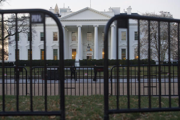 "In this March 24, 2019 photo, The White House is seen behind security barriers in Washington. A White House official turned whistleblower says dozens of people in President Donald Trump's administration were granted access to classified information despite ""disqualifying issues"" in their backgrounds including concerns about foreign influence, drug use and criminal conduct."