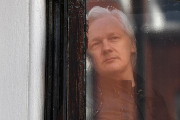WikiLeaks founder Julian Assange appears at the window of the balcony prior to making an address to the media at the Embassy of Ecuador in London on May 19, 2017.