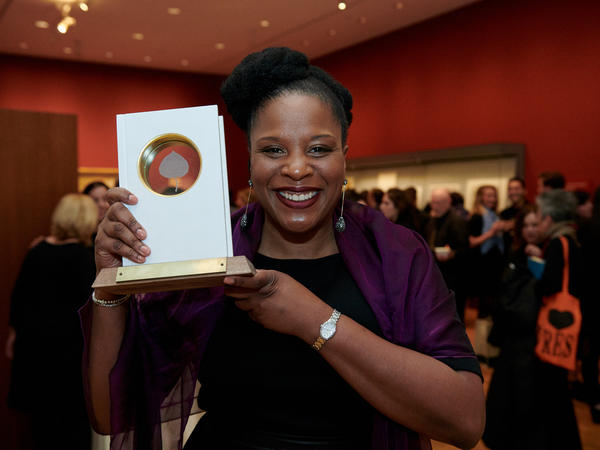 Tayari Jones holds up her Aspen Words Literary Prize, which she won Thursday in New York City for her novel <em>An American Marriage.</em>