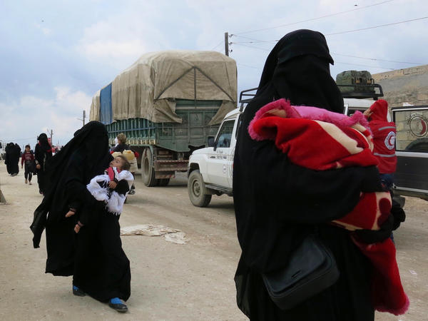 Women carry children near the al-Hol camp in Syria's Kurdish-majority region of Rojava. The camp is filled with more than 72,000 people — most of them women and children who came out of the last ISIS-held territory.