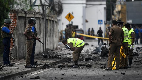 Sri Lankan security personnel inspect the debris of a van after it exploded on Monday near St. Anthony's Shrine in Colombo. More than 300 people died and more than 500 were wounded after Sunday's attacks on churches and hotels.
