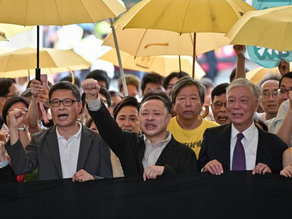 """Sociology professor Chan Kin-man (left), law professor Benny Tai (center), and Baptist minister Chu Yiu-ming (right) chant slogans before entering the West Kowloon Magistrates Court in Hong Kong on Wednesday to receive their sentences after being convicted on """"public nuisance"""" charges for their role in organizing mass pro-democracy protests in 2014."""