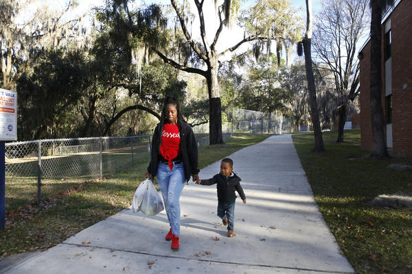 Akiya Parks, a senior at the University of Florida, and her 3-year-old son Caleb, walk through campus.
