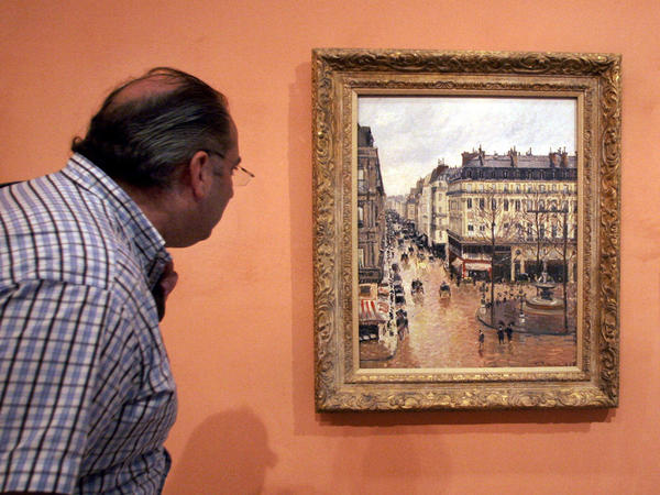 A visitor in 2005 views the impressionist painting called <em>Rue St.-Honore, Apres-Midi, Effet de Pluie,</em> painted in 1897 by Camille Pissarro, on display in the Thyssen-Bornemisza Museum in Madrid.