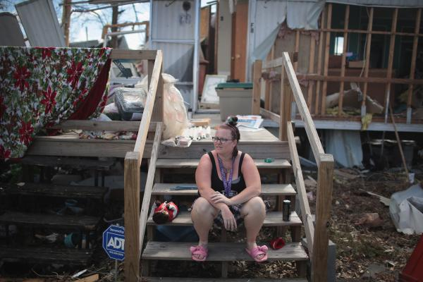Kimbrely Brock sits on the steps of a friend's trailer that was destroyed by Hurricane Michael in Panama City, Fla., in October. President Trump holds a political rally in Panama City Wednesday.