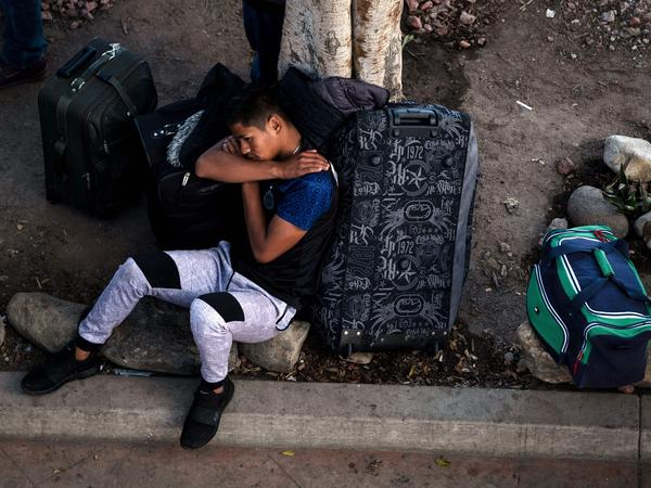 An asylum-seeker rests outside El Chaparral port of entry while he waits for his turn to present himself to U.S. border authorities to request asylum, in Tijuana, Mexico, last month. A federal appeals court has granted the Trump administration's request to temporarily allow the government to continue to return asylum-seekers to Mexico while it appeals an ruling that blocked the policy.