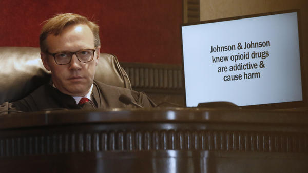 Judge Thad Balkman listens during opening arguments for the state of Oklahoma on Tuesday in Norman, Okla. It is the nation's first state trial against drugmakers blamed for contributing to the opioid crisis begins in Oklahoma. At right is a slide from the state's presentation shown on a monitor.