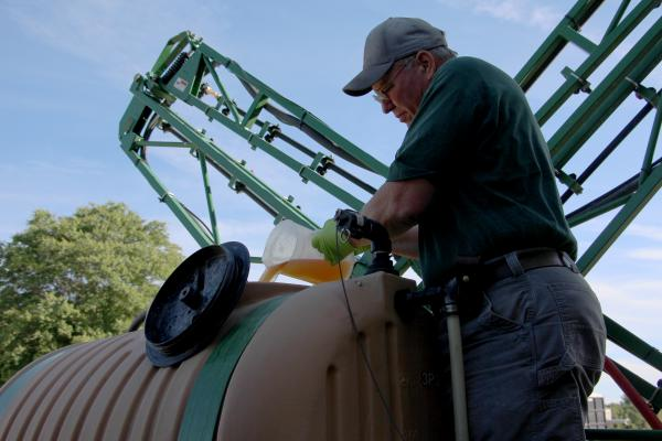 John Draper pours glyphosate into the tank of his sprayer at the University of Maryland's Wye Research and Education Center.