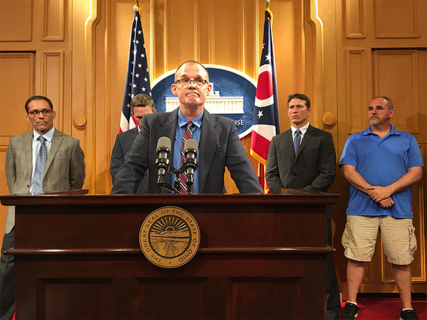 Roger Beedon (center) speaks about the sexual abuse he says Richard Strauss inflicted on him. Behind him are former All-American wrestler Mike Schyck, Brian Garrett, who worked at a clinic operated by Strauss and two other survivors.