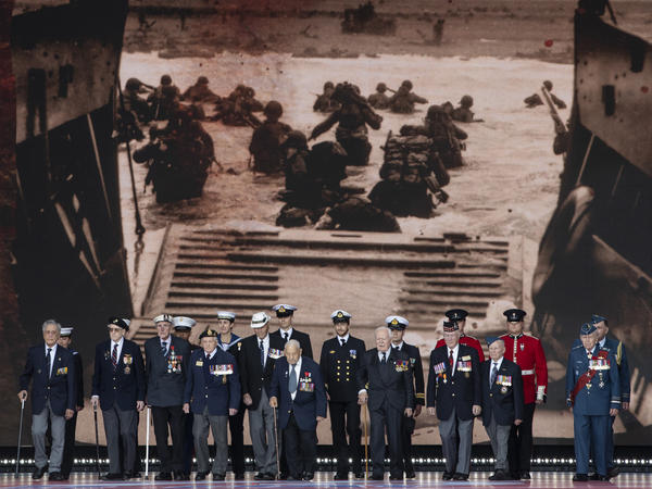 Veterans stand in front of a 1944 image of their comrades wading onto the beaches of France during D-Day commemorations in Portsmouth, England. Leaders of 16 countries involved in World War II joined Queen Elizabeth II at the ceremony on Wednesday.