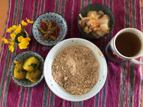 A bowl of tsampa flour pictured with other dishes in a typical Tibetan lunch. Counterclockwise from left: potatoes in turmeric and cumin; <em>liangfen;</em> mung bean jelly and spring onions with cilantro, triple-fried in red chili pepper; and black tea. To make <em>pa</em>, the tsampa would be mixed with butter, tea, salt and sometimes Tibetan cheese.