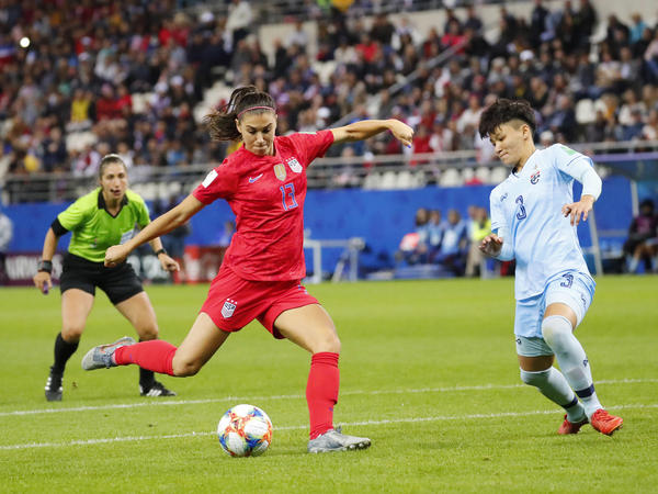 U.S. forward Alex Morgan shoots and scores past Thailand's Natthakarn Chinwong on Tuesday in Reims, France, in the group stage of the Women's World Cup.