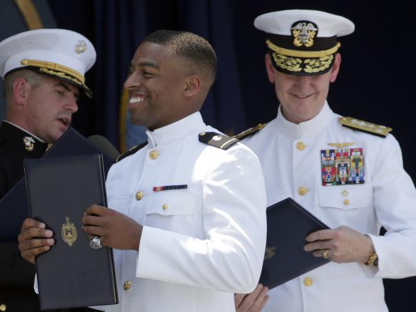 Keenan Reynolds (center), Baltimore Ravens' sixth round NFL draft pick, carries his diploma during the Naval Academy's graduation in May 2016. Trump's order on Wednesday would allow more military graduates to defer service in order to pursue professional sports careers.