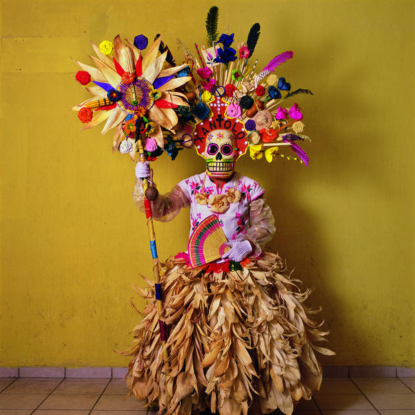This costume, with corn husks and feathers and paper flowers, is worn by a member of a dance group that gathers in cemeteries and other places to mark Day of the Dead festivities (called Xantolo, the word written above the mask). The idea of combining a skeletal mask with European fashion was devised by the Mexican artist Jose Guadalupe Posada, who lived in the 19th and early 20th centuries.