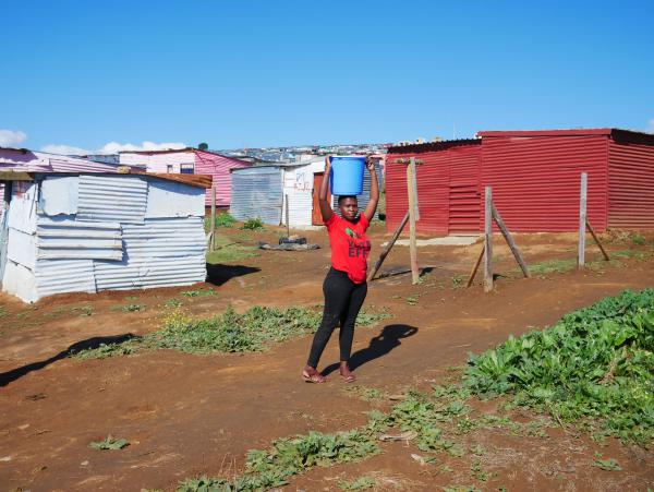 Annah Goba, 20, carries water to her shack in Azania, the name squatters gave to a section of private property they took over in Stellenbosch. Goba said the lack of running water was a challenge, but she couldn't afford to pay rent in crowded Kayamandi township. Her shirt is from the far-left Economic Freedom Fighters party, which encourages supporters to occupy the land of wealthy farm owners.