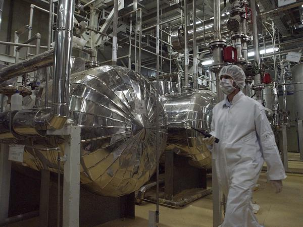An Iranian security official in protective clothing walks through a uranium conversion facility in 2005. Iran says it is now enriching uranium above the limit set in the 2015 nuclear deal.