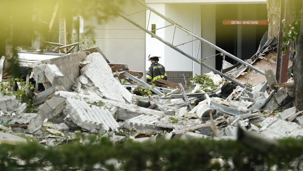 An official walks near debris after an explosion on Saturday in Plantation, Fla. Approximately 20 people are reported to have been injured in the blast.