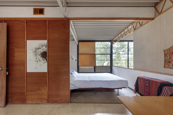 The master bedroom as viewed from the guest bedroom. The sliding wood panel at left could open to create one large bedroom space.