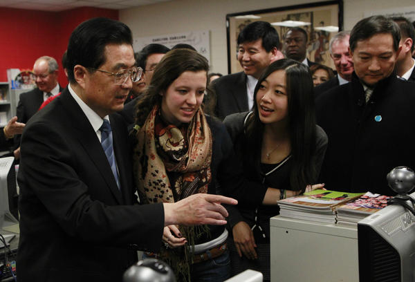 In this 2011 photo, Hu Jintao, then China's president, visits the Confucius Institute at the Walter Payton College Preparatory High School in Chicago. China established more than 100 Confucius Institutes, which provide language and culture programs, at U.S. schools. But at least 13 universities have dropped the program due to a law that raises concerns about Chinese spying.