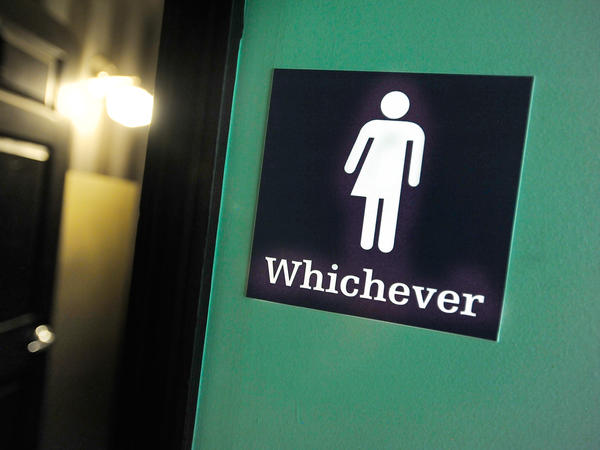 """A gender-neutral sign is posted outside a bathrooms at a restaurant in Durham, N.C. Many North Carolina businesses put gender-neutral signs on toilets after the """"bathroom bill"""" was passed."""