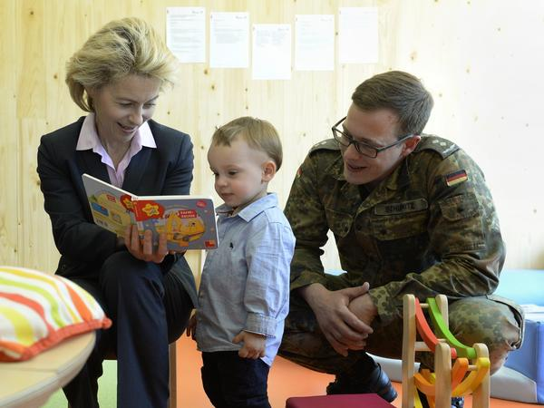Ursula von der Leyen, then Germany's defense minister, reads in 2014 with 1st Lt. Patrick Schumitz and his son, Oskar, during a nursery opening at the University of the Federal Armed Forces, Munich. During a previous stint running Germany's family ministry, von der Leyen, a mother of seven, instituted new child care and parental leave policies.