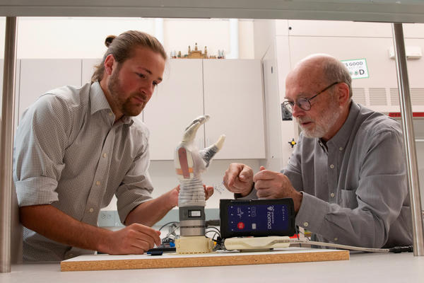 University of Utah doctoral student Jacob George, left, and associate professor Greg Clark examine the LUKE arm that they use for their experiments. A man who lost his lower arm in an electrical accident was able to experience some sense of touch and fine motor control with his grip while using the experimental device.