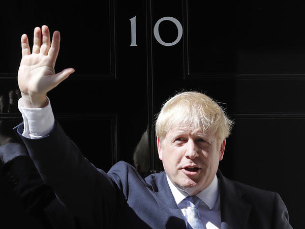 Boris Johnson waves outside 10 Downing Street in London on Wednesday. The polarizing and showboating new prime minister has vowed to deliver on the U.K. leaving the European Union in October, whether or not a deal is reached.