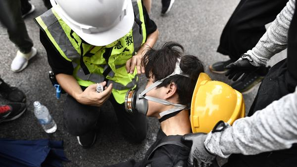 A protester helps a fellow demonstrator after police fired tear gas in the district of Yuen Long in Hong Kong on Saturday. Demonstrators defied a police ban to rally.