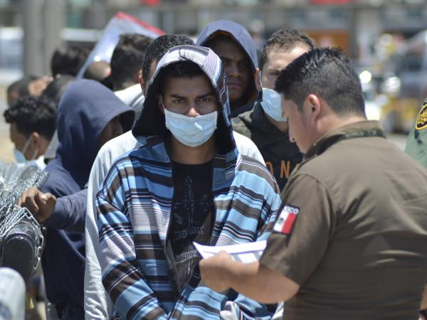 U.S. Border Patrol officers return a group of asylum-seeking migrants to Mexico as Mexican officials check the list, in Nuevo Laredo.