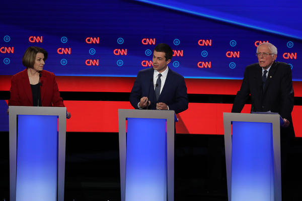 Democratic presidential candidate South Bend, Ind., Mayor Pete Buttigieg (center), speaks while Sens. Amy Klobuchar and Bernie Sanders listen during the Democratic presidential debate in Detroit on Tuesday. All three agree on the need to ban assault-style weapons and for a universal background check for gun buyers.