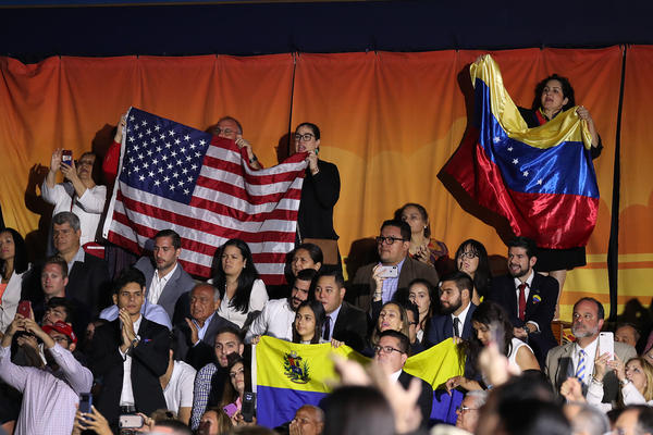 People listen as President Trump speaks during a Feb. 18 rally at Florida International University in Miami, where he addressed the crisis in Venezuela. Trump's administration is considering protected status for Venezuelans living in the U.S.