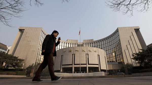 A man walks past China's central bank, which appears to have orchestrated the yuan's fall against the U.S. dollar.