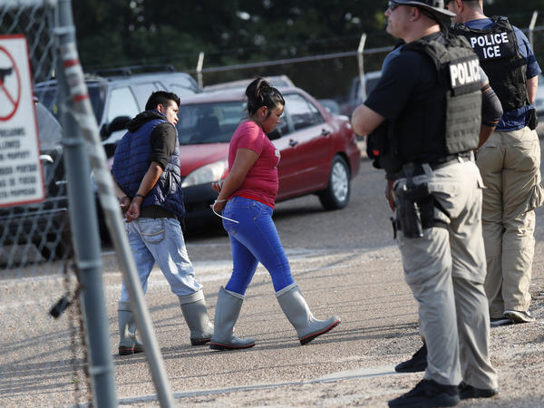 Two people are taken into custody by ICE agents at a Koch Foods Inc. plant in Morton, Miss., one of seven food processing plants targeted for coordinated raids in the state.