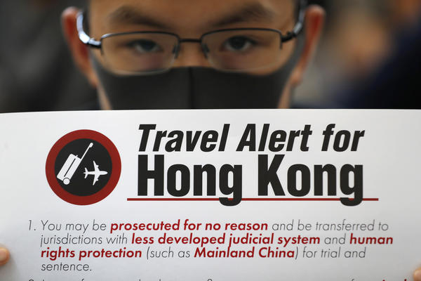 A pro-democracy protester holds up a banner waning travelers at the airport in Hong Kong on Friday.
