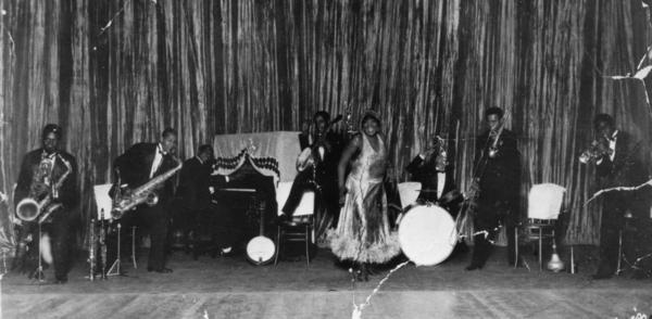Bessie Smith on stage with her band in Philadelphia, Penn. Smith infused her performances with glamour whether she was performing in cities or for rural audiences in settings that evoked minstrelsy.