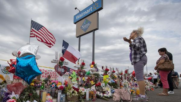 A woman prays at a makeshift memorial for shooting victims at the Cielo Vista Mall Walmart, in El Paso, Texas.