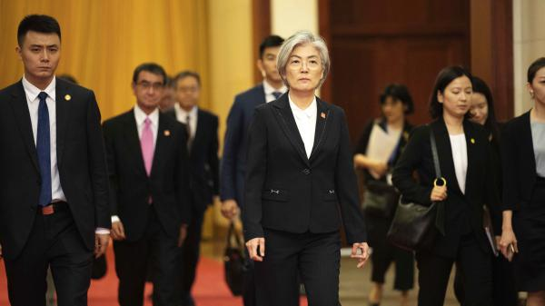 South Korea has announced it will withdraw from a 2016 military intelligence-sharing pact with Japan. Here, South Korean Foreign Minister Kang Kyung-wha, center, and Japanese Foreign Minister Taro Kono, trailing at left, walk in Beijing's Great Hall of the People on Thursday.