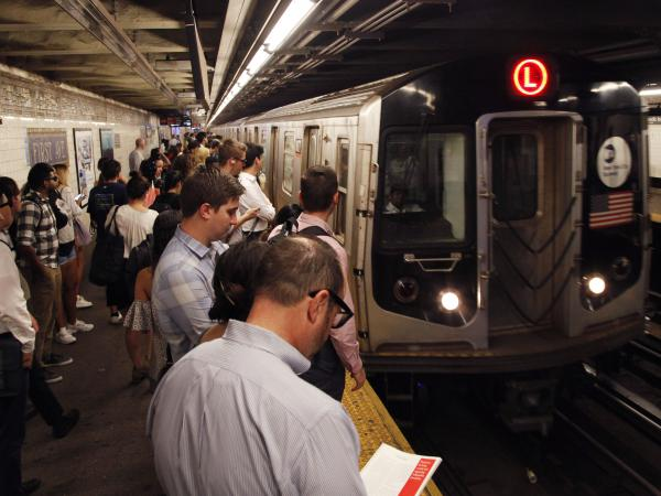 Straphangers wait for an L Train in New York City as it pulls into the First Avenue station. A bill under consideration might bar New York from replacing these cars with Chinese-made ones.