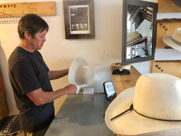 Charlie Rutledge works on shaping a new hat in his store in downtown Paonia. True West Hats recently launched an online store after getting a faster internet connection.