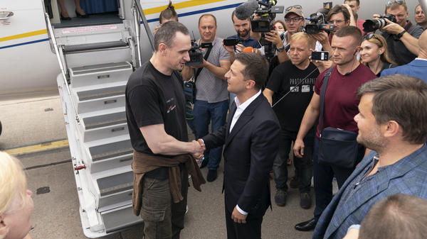 Ukraine's President Volodymyr Zelenskiy (right) greets Ukrainian prisoner filmmaker Oleg Sentsov upon his arrival in Ukraine on Saturday.