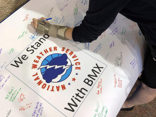 Christina Crowe signs a poster in support of the National Weather Service office in Birmingham, Ala., during a convention of the National Weather Association.