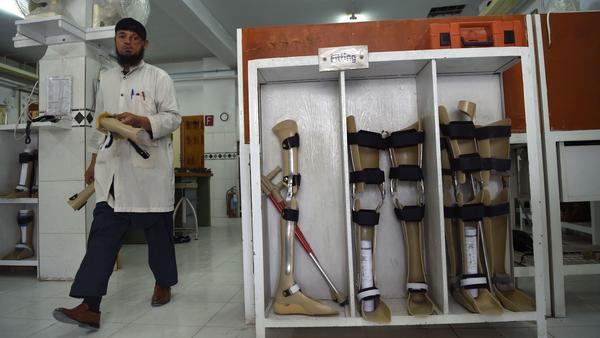 The Taliban say the Red Cross may resume its work in Afghanistan, more than five months after threatening the group. In this photo from March, an orthopedic technician walks past artificial limbs in a workshop at the International Committee of the Red Cross hospital for war victims and the disabled in Kabul.