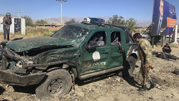 Afghan police inspect the site of a bombing in Parwan province, where Afghan President Ashraf Ghani was speaking at a campaign rally. The Taliban has claimed responsibility for the attack.