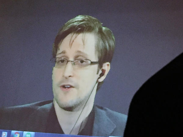 The Justice Department says Edward Snowden, seen here via video feed, breached nondisclosure agreements he signed with the National Security Agency and CIA with the publication of his new memoir, <em>Permanent Record</em>.